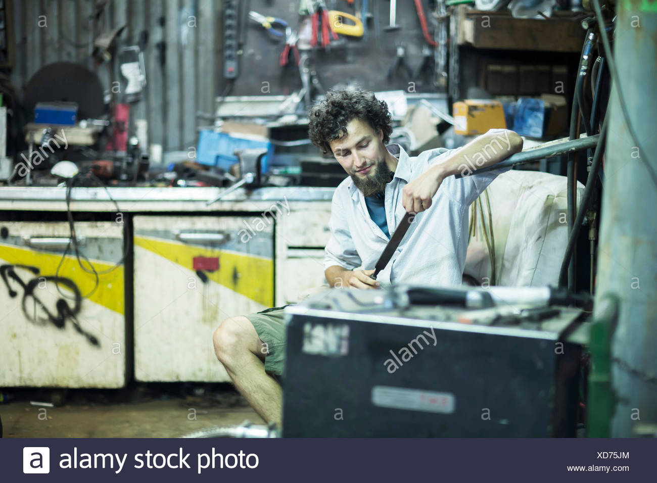 Young man with chin beard in alternative technical room - Stock Image