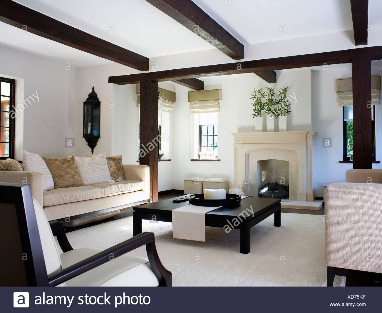 Beige Sofa And Large Black Coffee Table In Modern White Cottage Living Room With Stone Fireplace And White Carpet Stock Photo Alamy