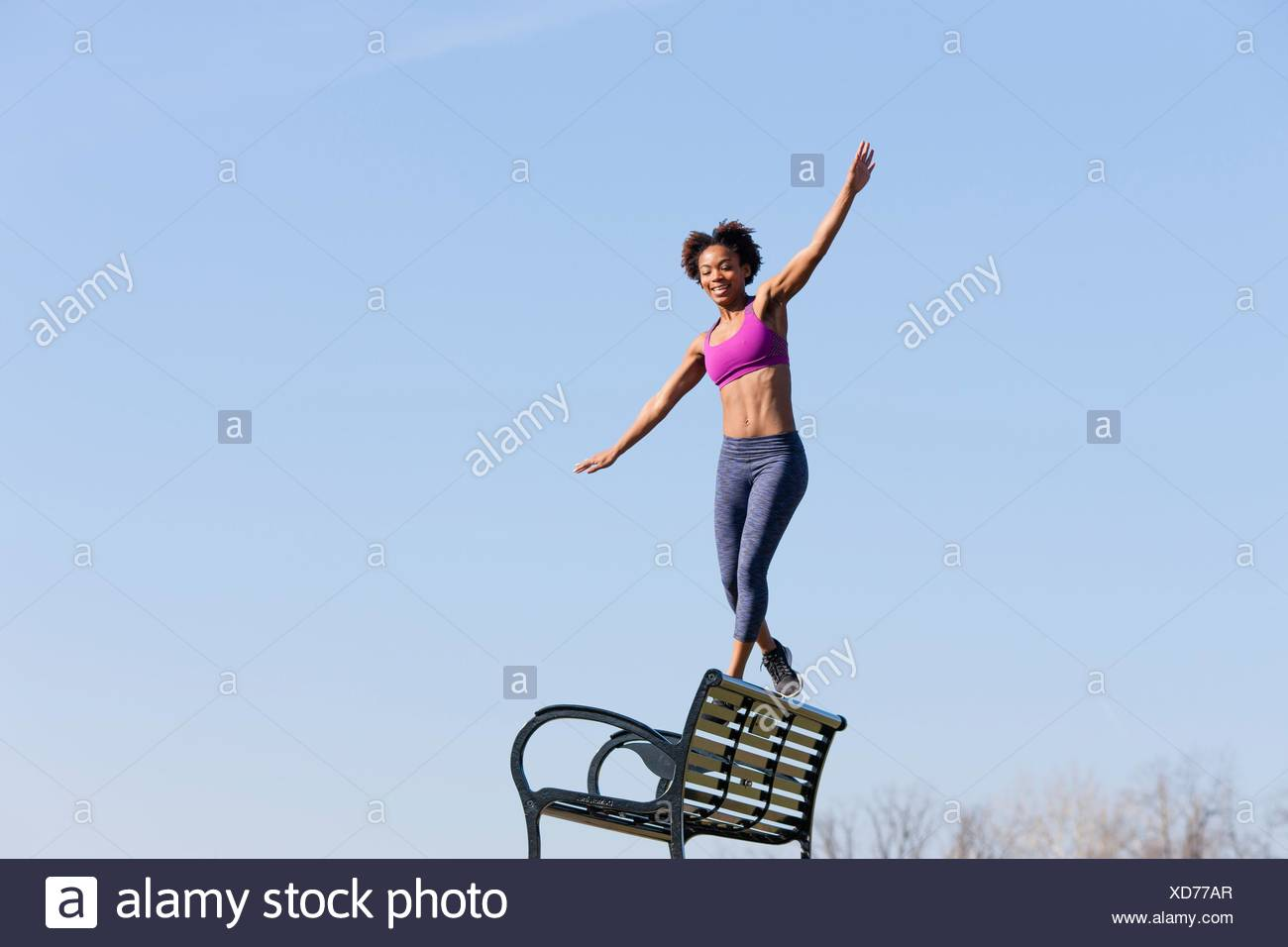 Young woman walking along edge of bench - Stock Image