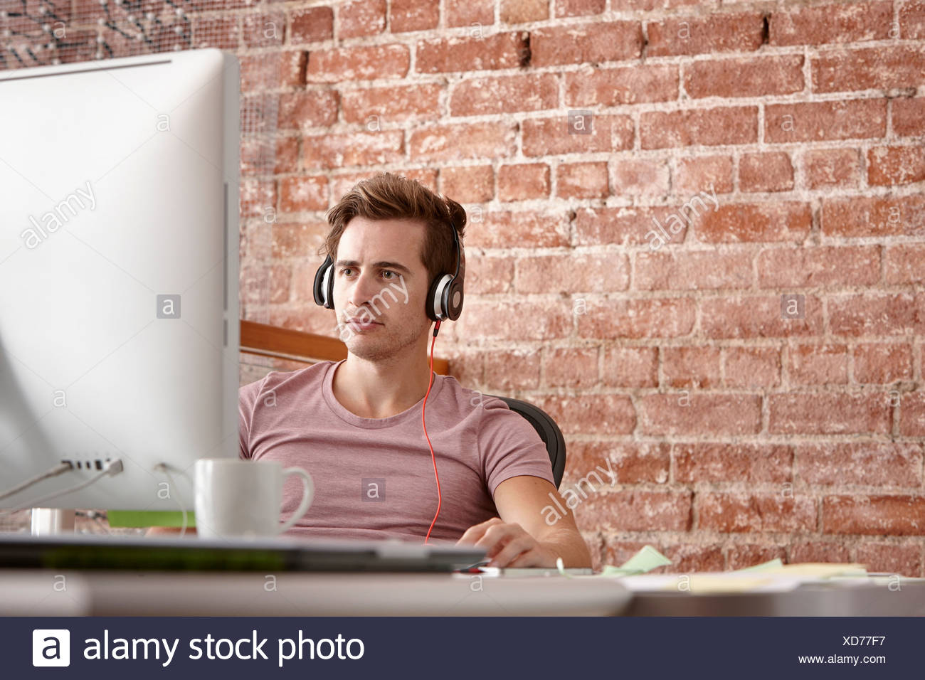 Young man using computer wearing headphones - Stock Image