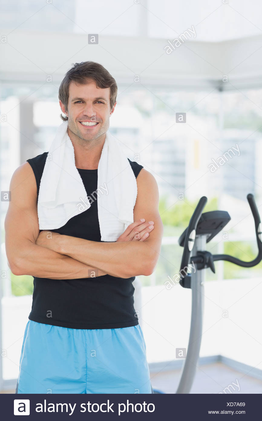Smiling man with arms crossed at spinning class in bright gym - Stock Image