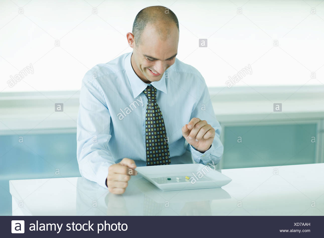 Man sitting in front of plate containing vitamins - Stock Image