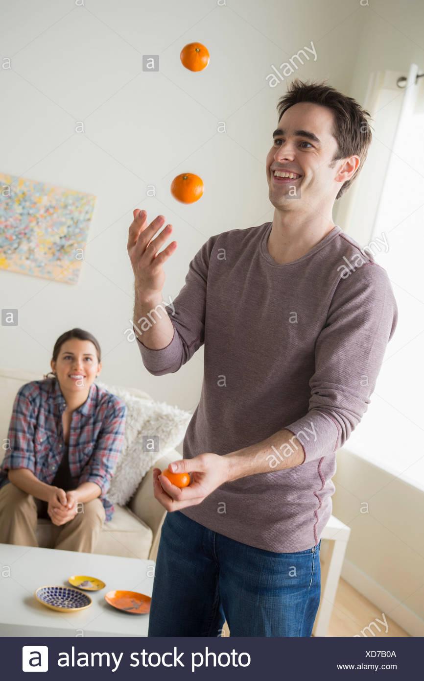 Man juggling oranges, woman watching - Stock Image