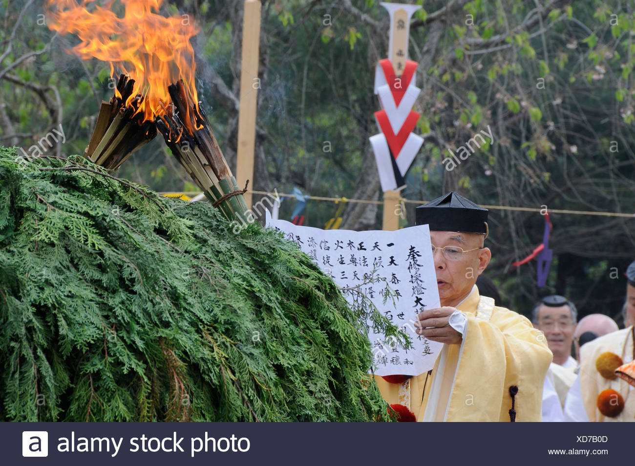 A Yamabushi master of ceremonies preaches in front of the fire mound and the ready lit torches, Kyoto, Japan, Asia - Stock Image