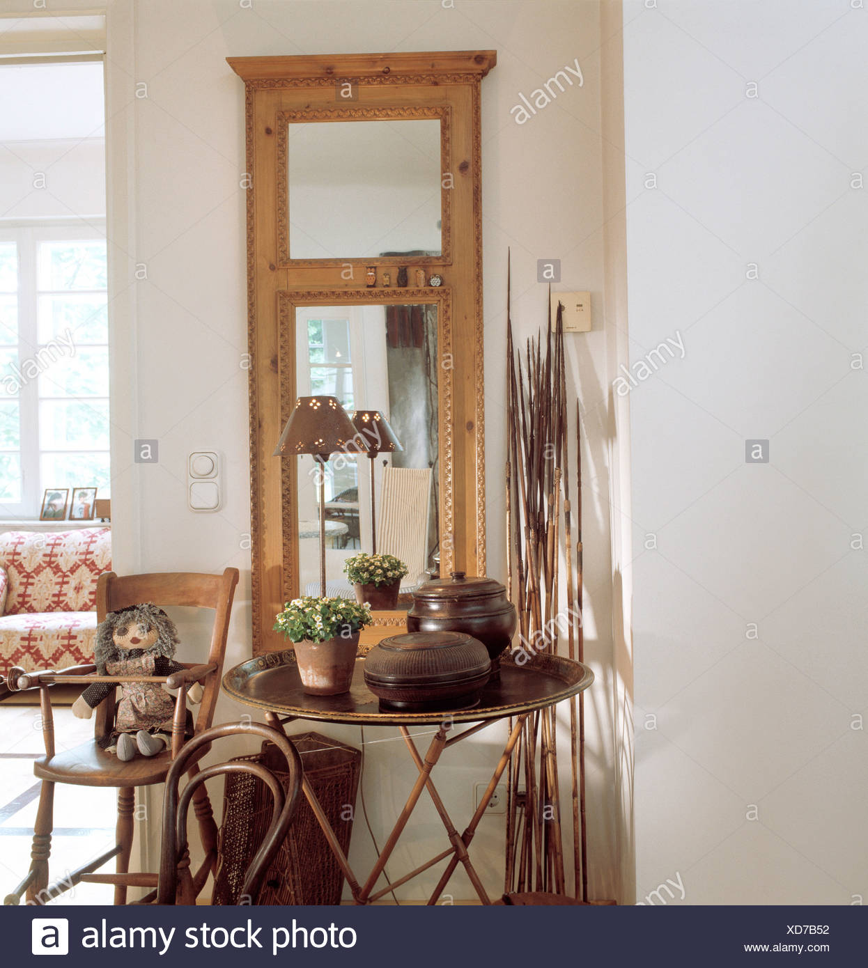 REAL HOMESDetail of hallway, with wood framed mirror, small table and chair, high chair, small lamp and decorative twigs - Stock Image