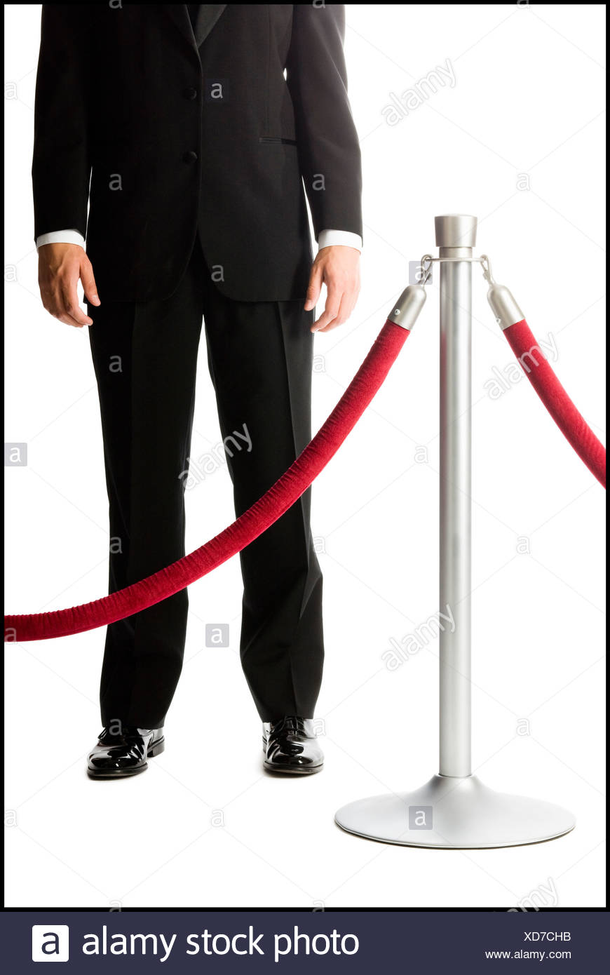 man in a tuxedo next to a velvet rope - Stock Image