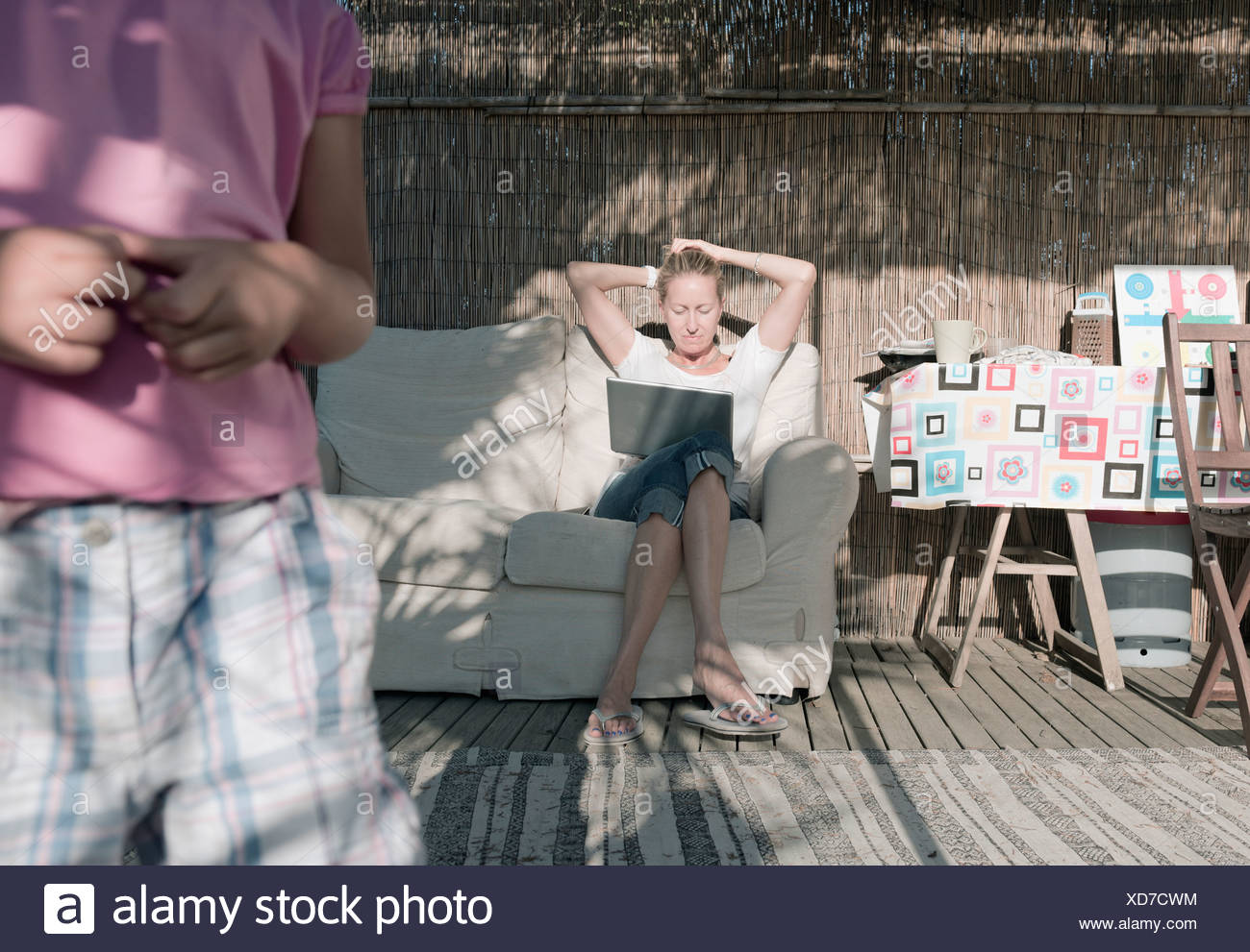 A Woman Sits On A Couch With Her Son In The Foreground; Tarifa, Cadiz, Andalusia, Spain - Stock Image
