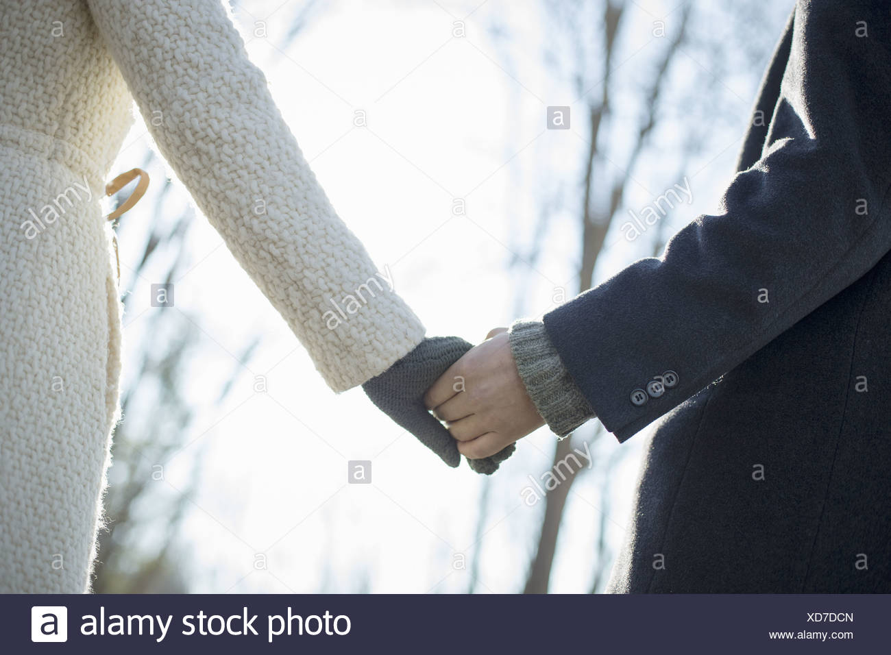 Two people, a couple, a man and woman in the woods on a winter day. Holding hands. - Stock Image