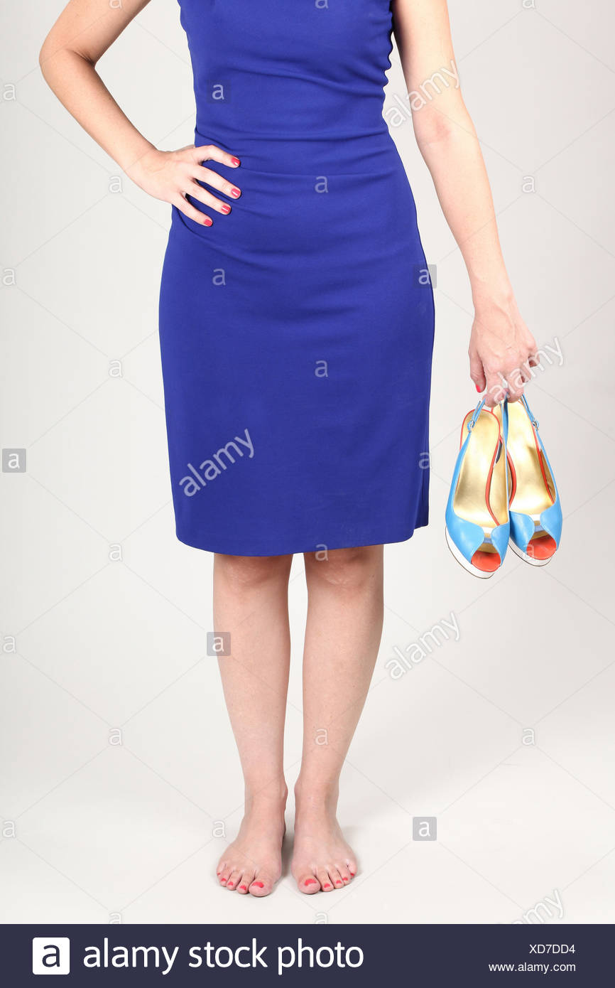 Woman in blue dress holds her high heel shoes - Stock Image