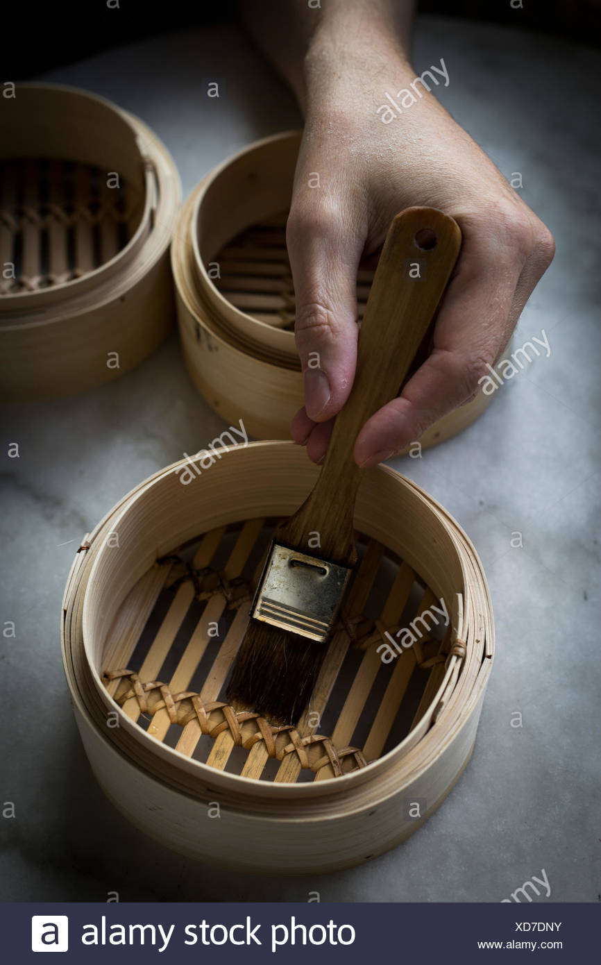 Man's hand greasing bamboo steamers on marble tabletop with a brush - Stock Image