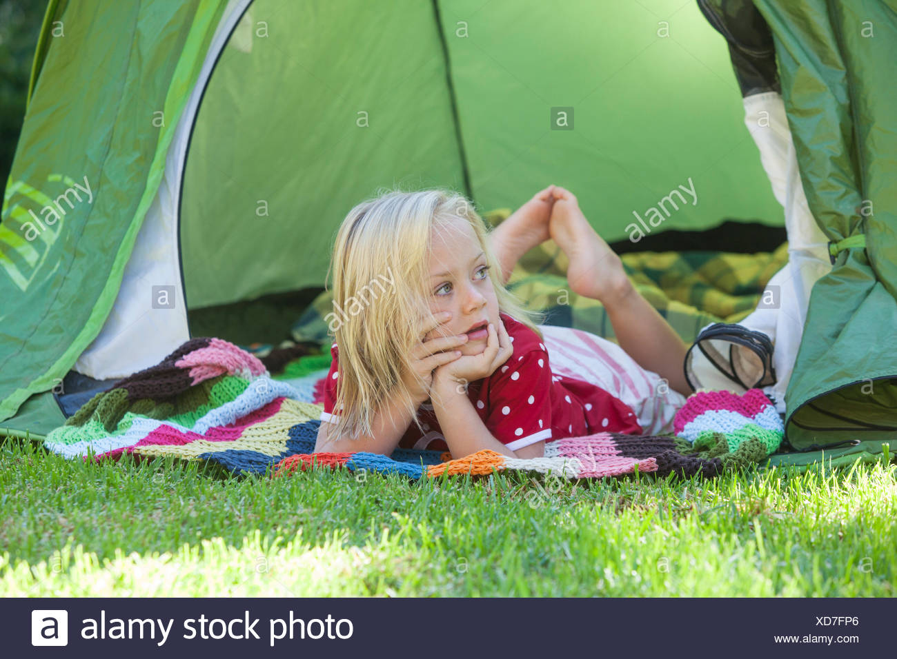Portrait of girl daydreaming in garden tent - Stock Image