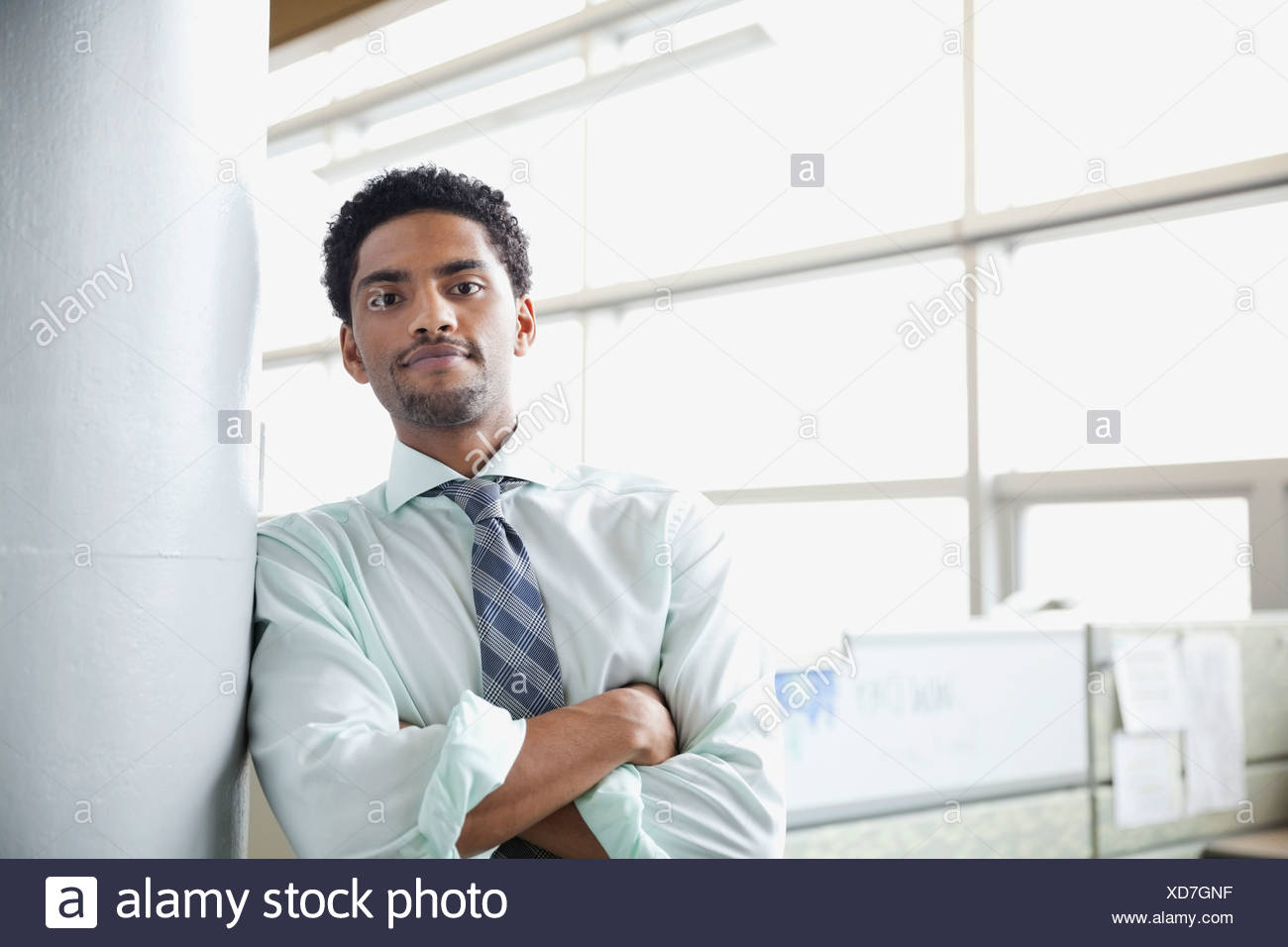 Confident businessman leaning against column - Stock Image