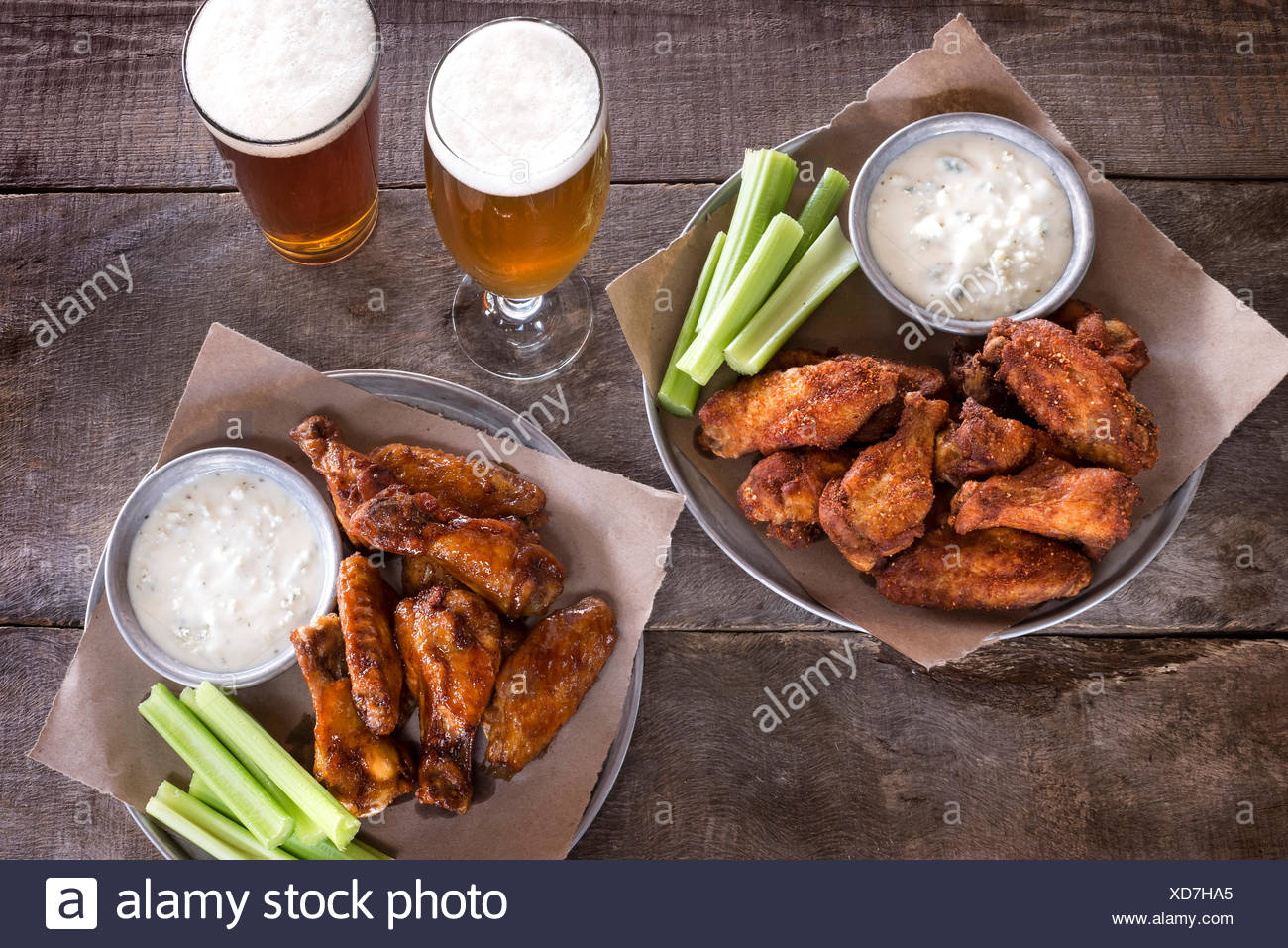 Two trays of wings and two glasses of beer on a rustic wood surface. - Stock Image