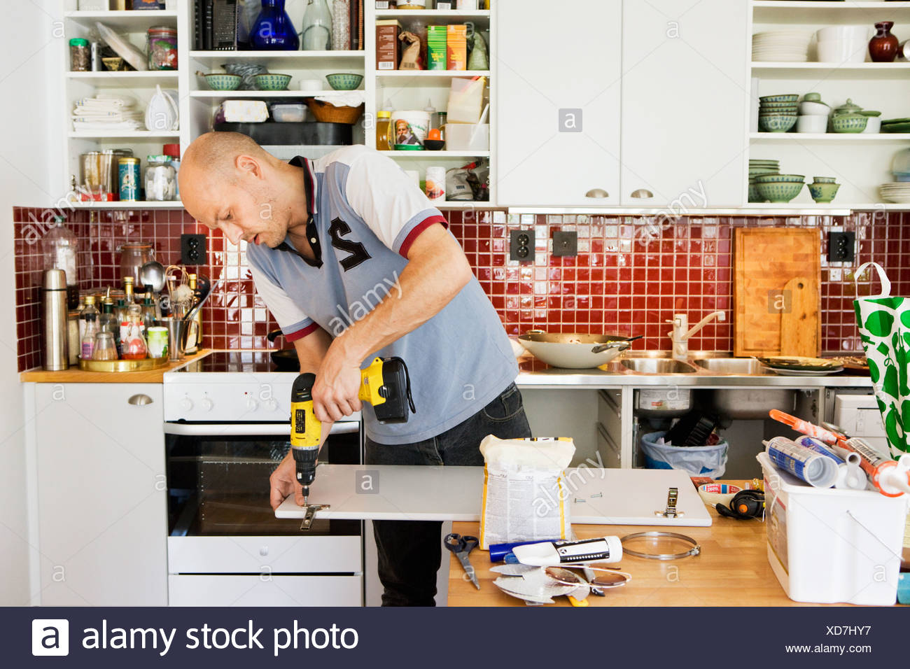 Mid Adult Man Using Drill And Repairing Furniture