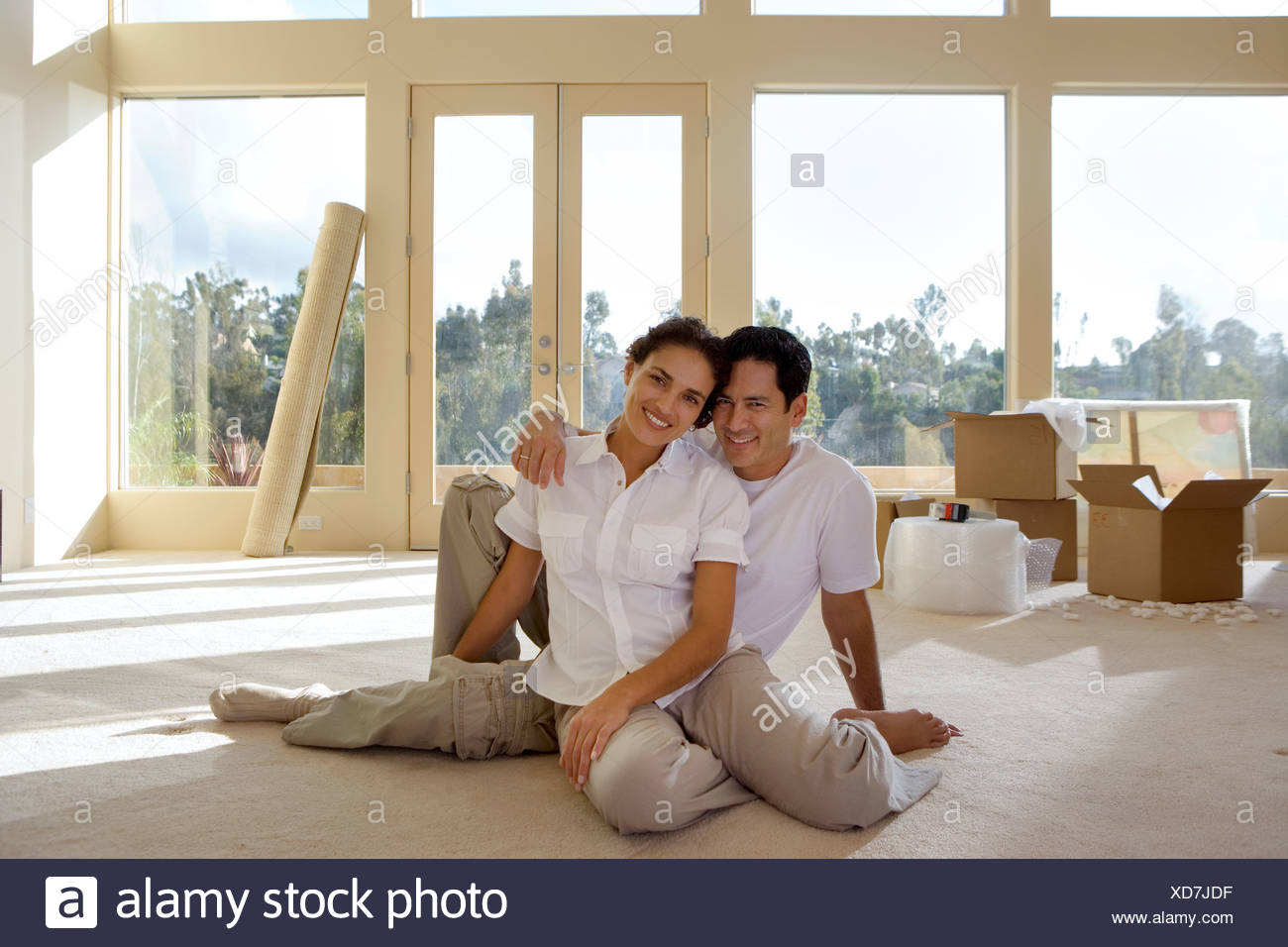 Couple moving house sitting on bare living room floor man with arm around woman smiling portrait - Stock Image
