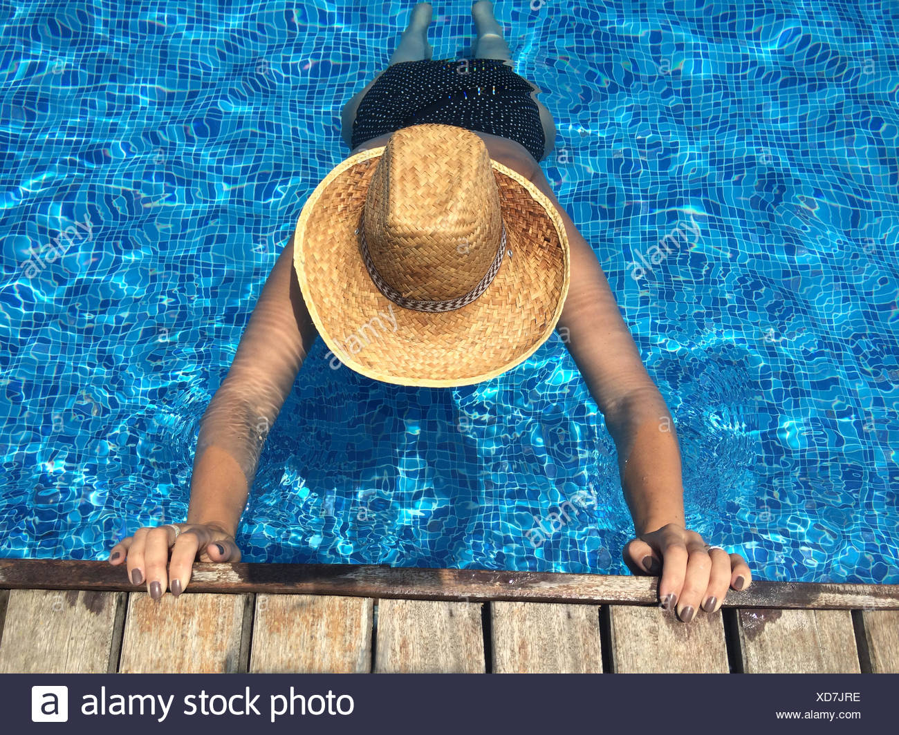 Woman stretching in swimming pool - Stock Image