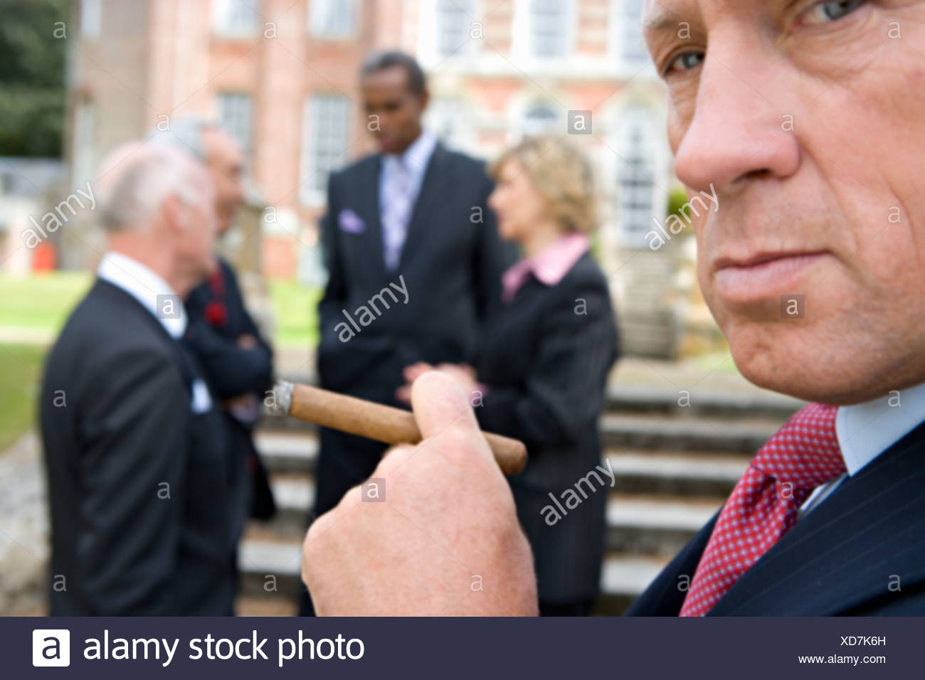 Businessman with cigar by manor house, colleagues in background, close-up Stock Photo