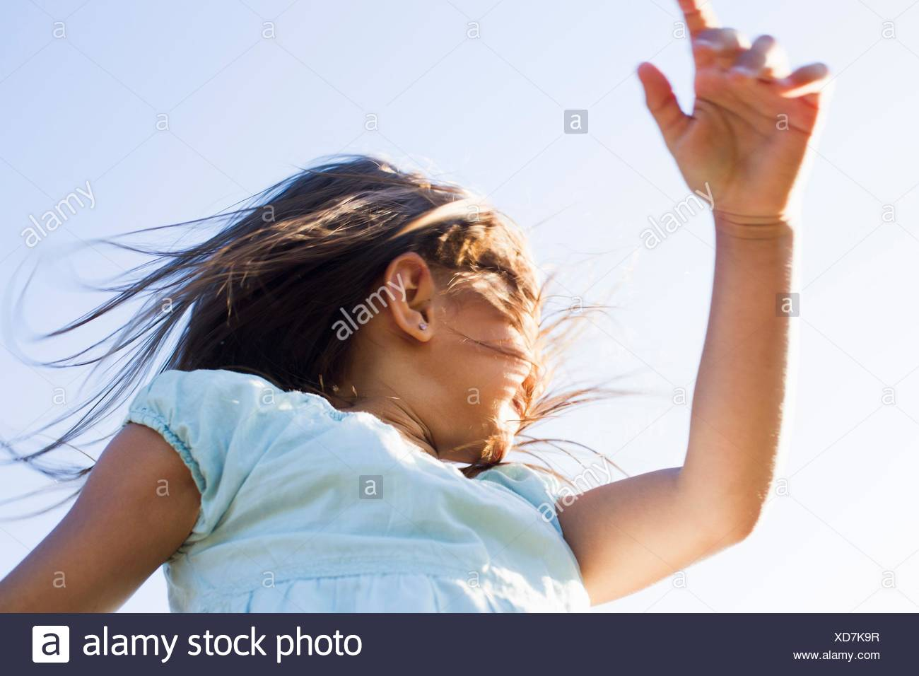 Low angle view of girl spinning around against blue sky - Stock Image