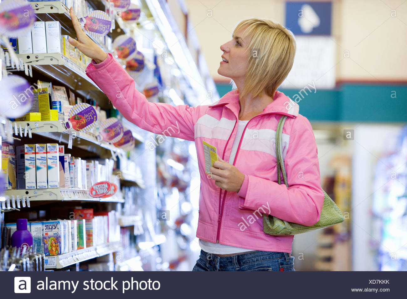 Woman shopping in supermarket choosing item from shelf side view - Stock Image