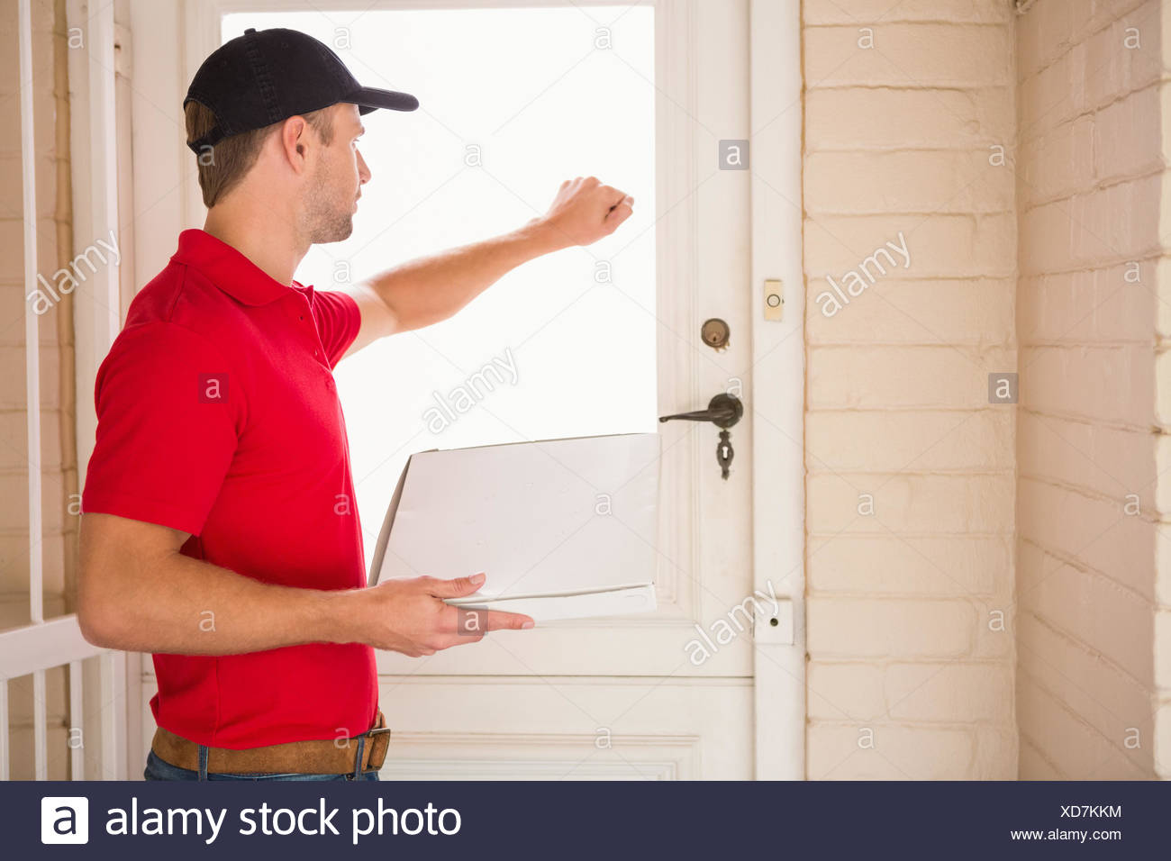 Delivery man holding pizza while knocking on the door & Delivery man holding pizza while knocking on the door Stock Photo ...