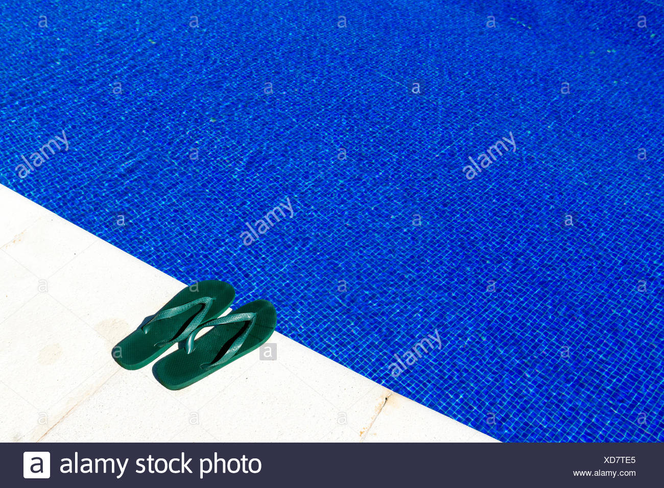 Swimming pool with flip-flops - Stock Image