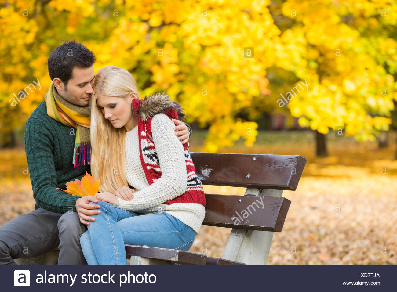 Loving young man hugging shy woman on park bench during autumn - Stock Image