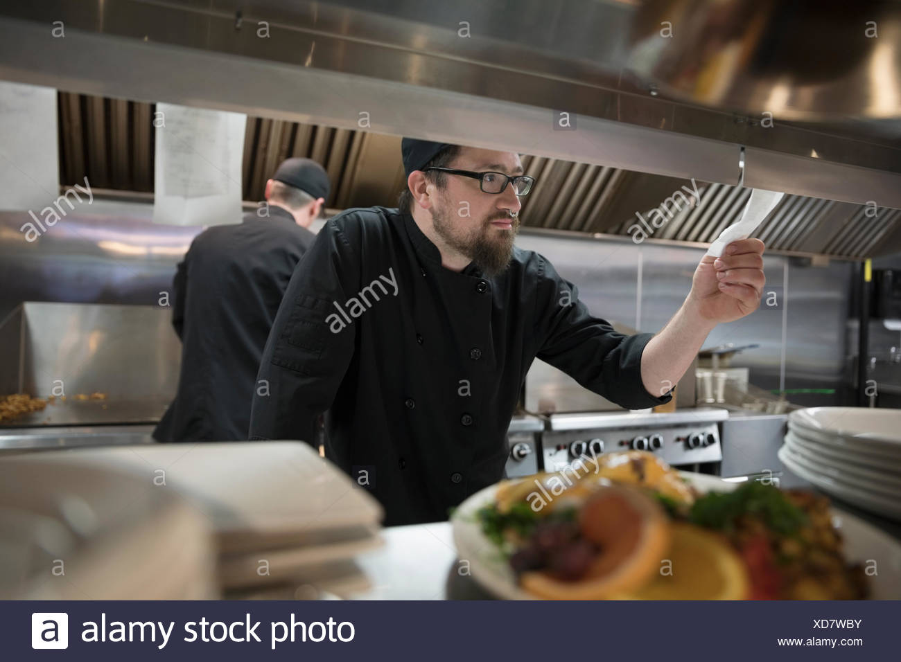 Line cook checking order, preparing food in restaurant kitchen - Stock Image