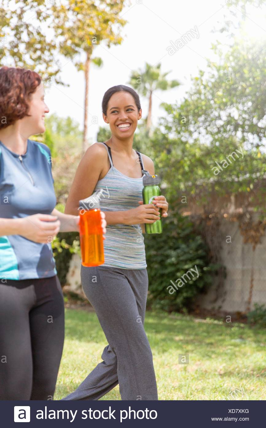 Young women out walking wearing sports clothing carrying water bottles laughing - Stock Image