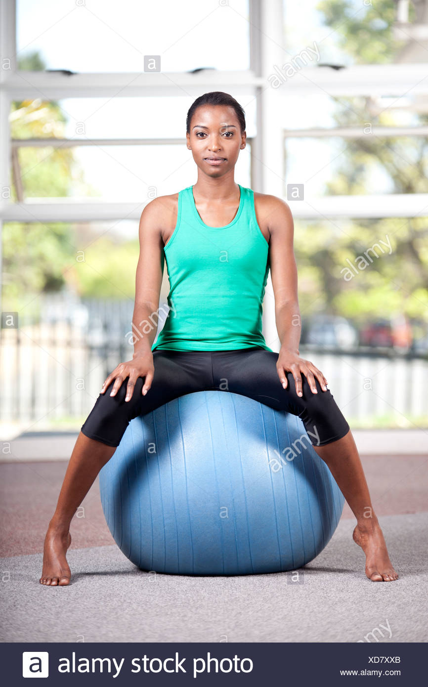 Young black female sits on an exercise ball in a gym - Stock Image
