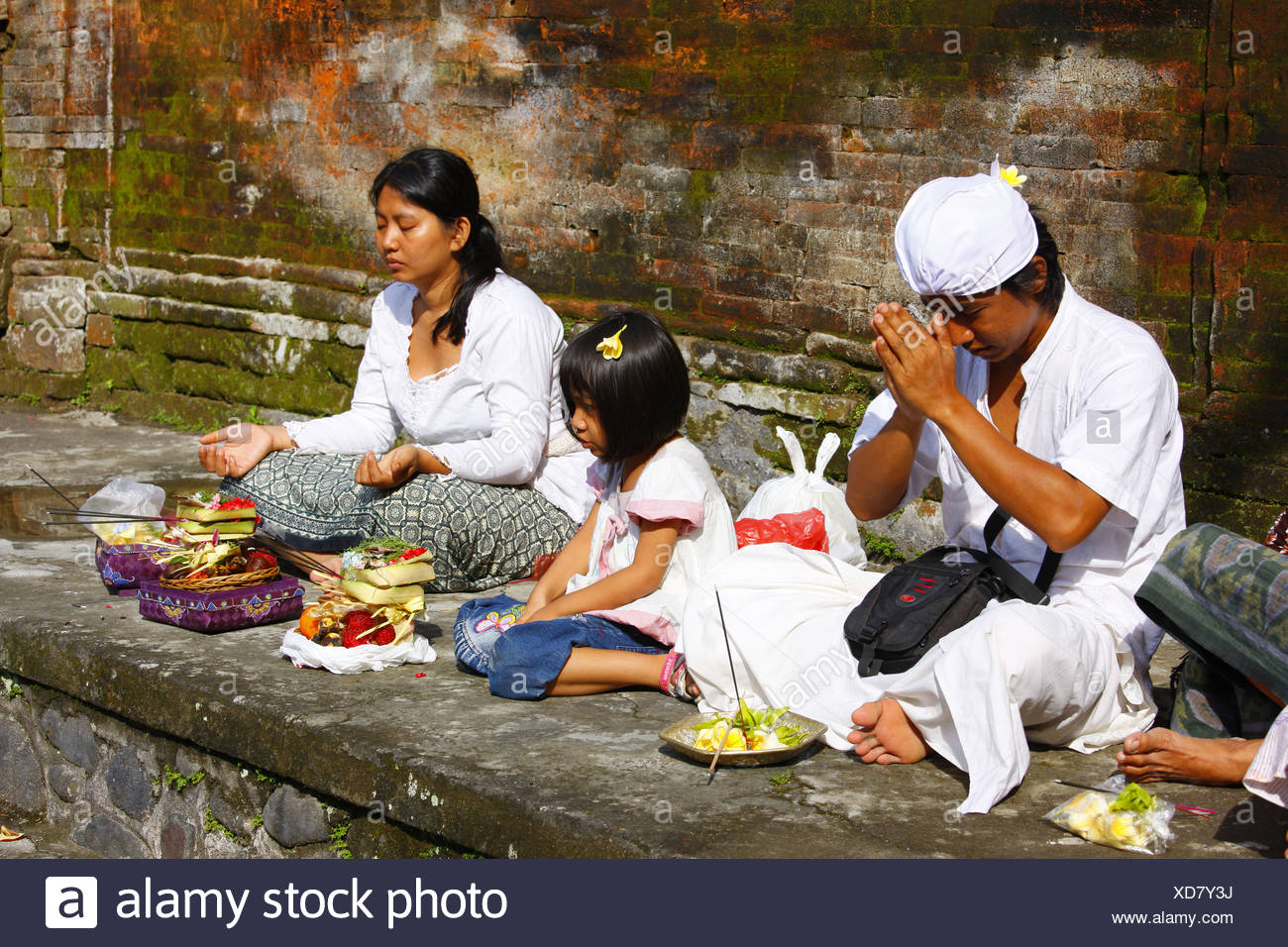 People at a ceremony at a sacred spring, Tirta Empul at Tampak Siring in the morning light, Bali, Republic of Indonesia, Southe - Stock Image