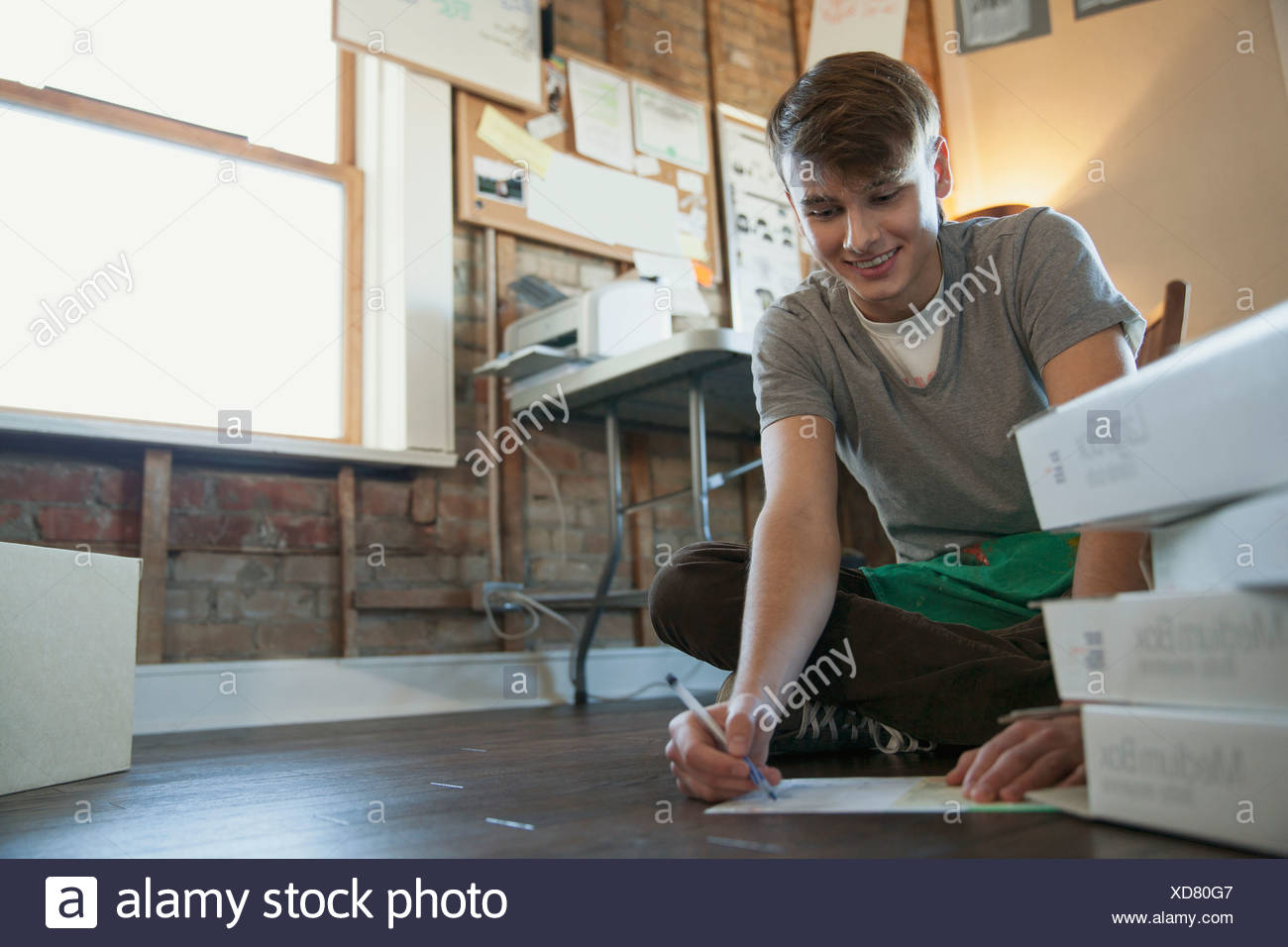 Male design professional sketching while sitting on floor - Stock Image
