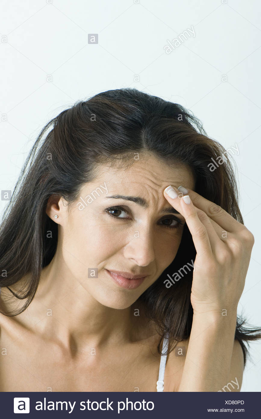 Woman holding head, looking at camera, portrait - Stock Image