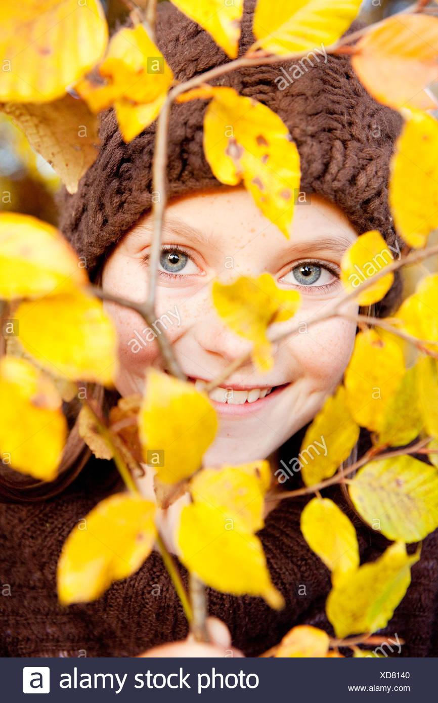 Girl behind a tree limb - Stock Image