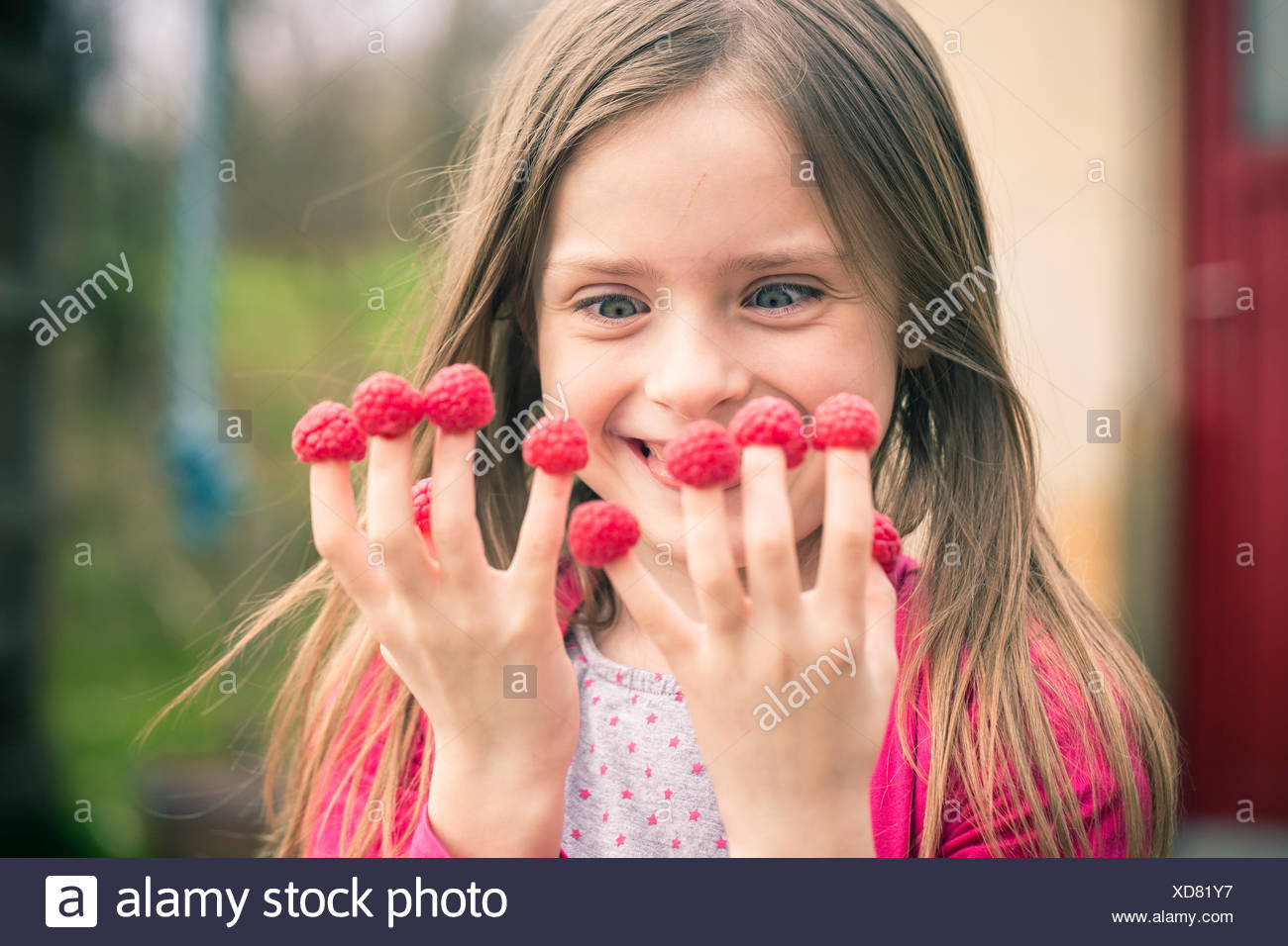 Happy girl with raspberries on her fingers Stock Photo