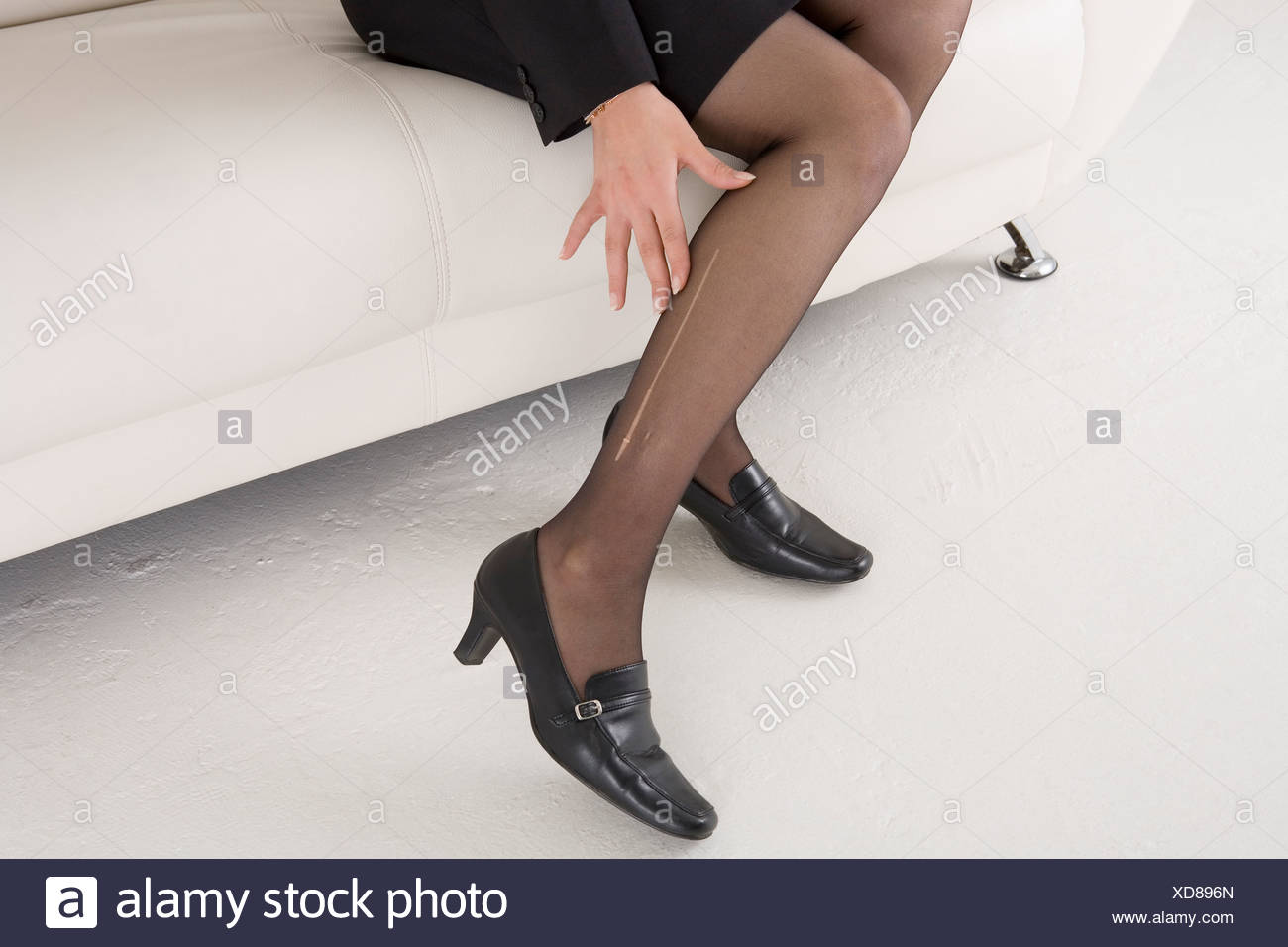 Young woman with laddered stockings - Stock Image