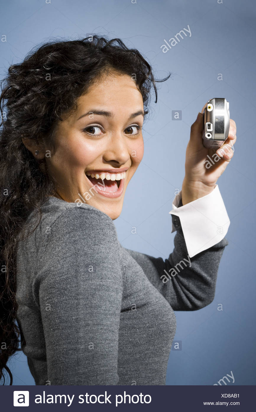 Woman taking a photo with digital camera smiling - Stock Image