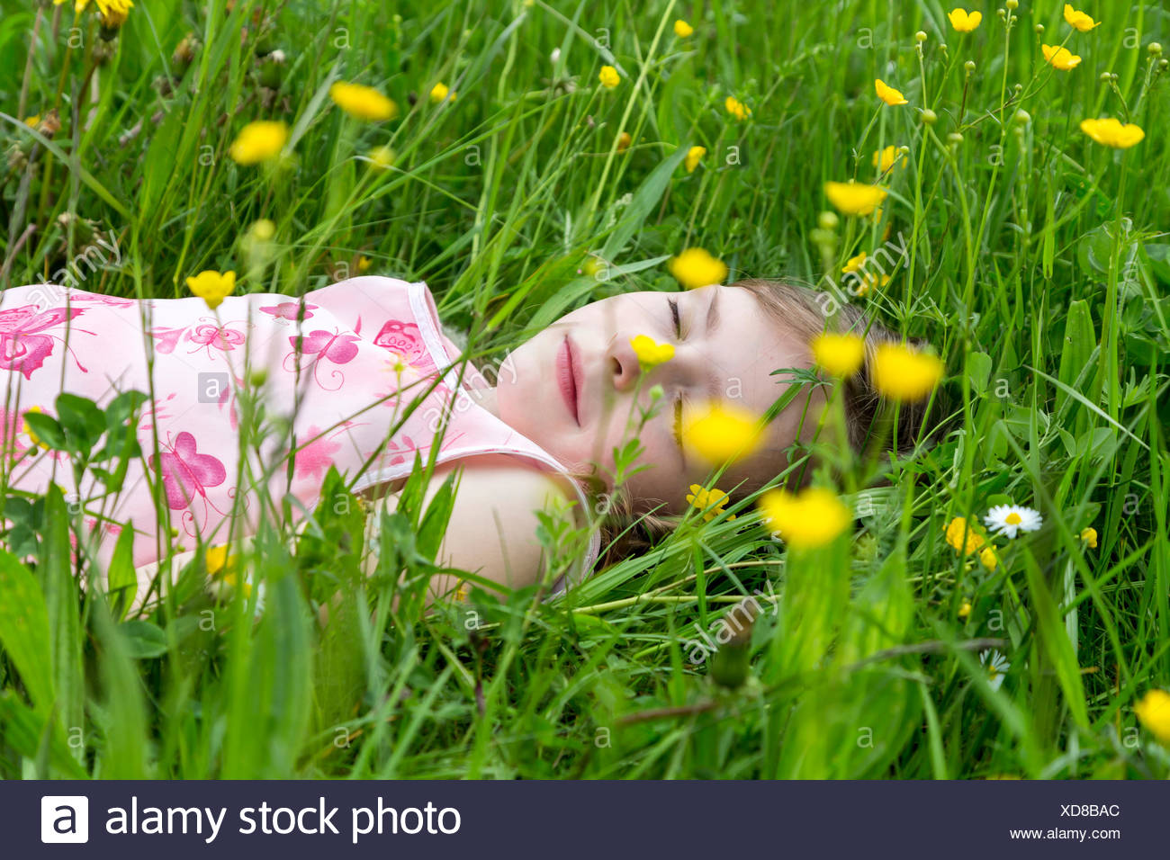 Little girl with closed eyes lying on a flower meadow Stock Photo