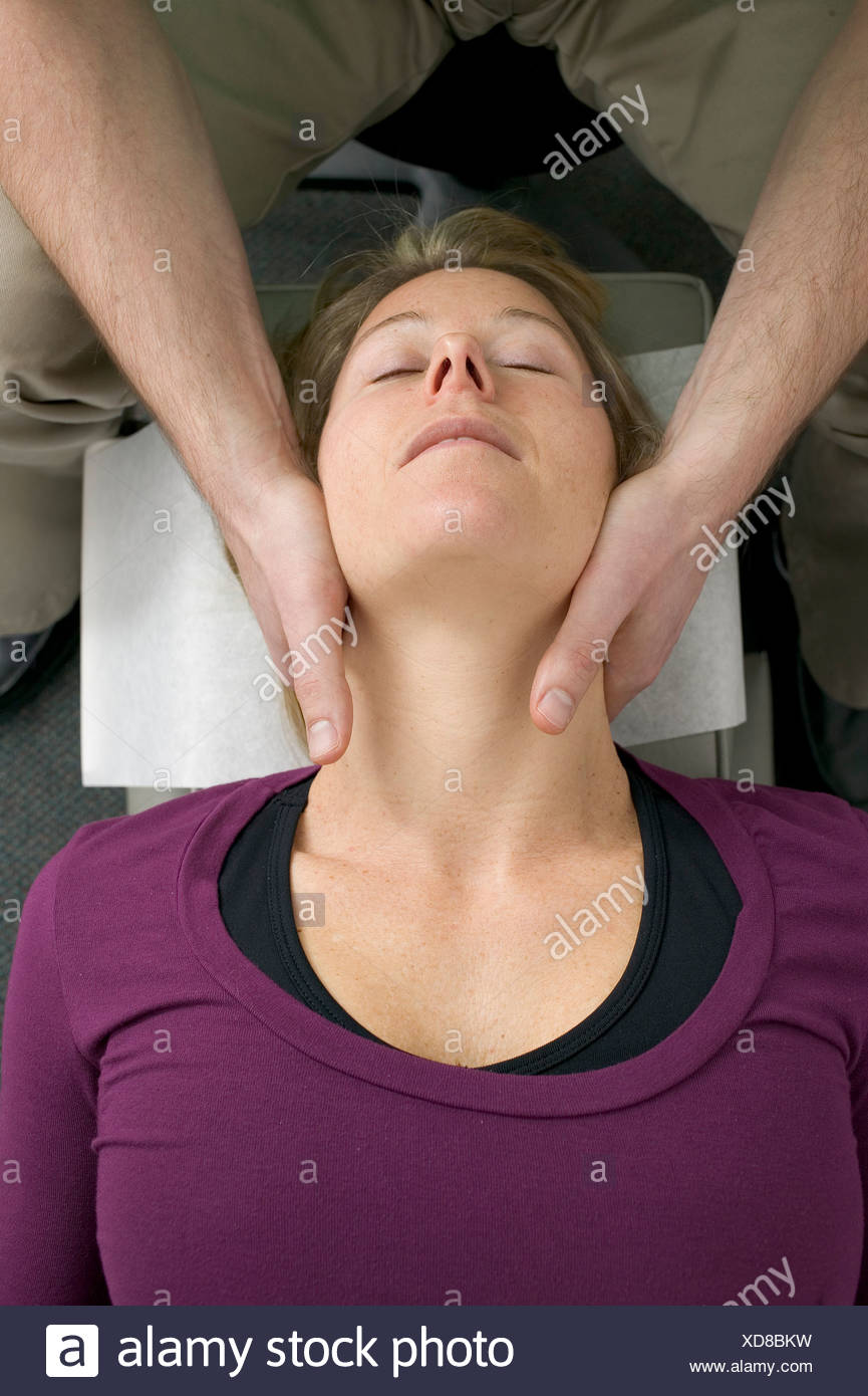 Masseuse massaging woman's neck Stock Photo