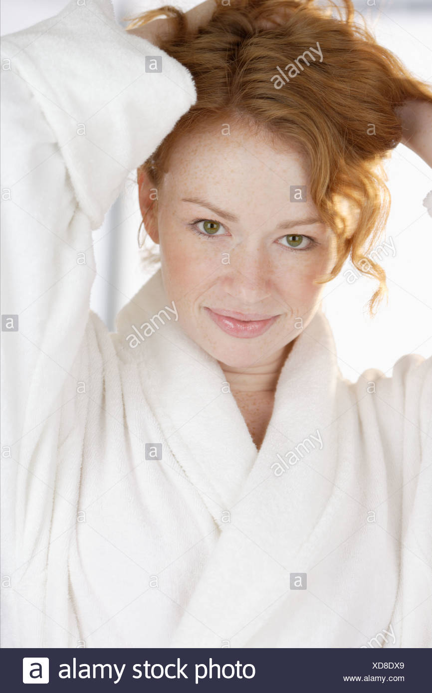 Woman in bathrobe holding hair up - Stock Image