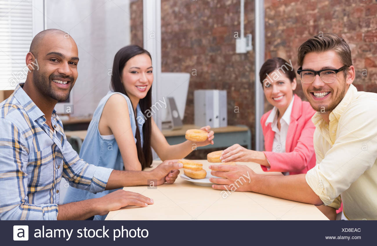 Business team taking doughnut during breaks - Stock Image