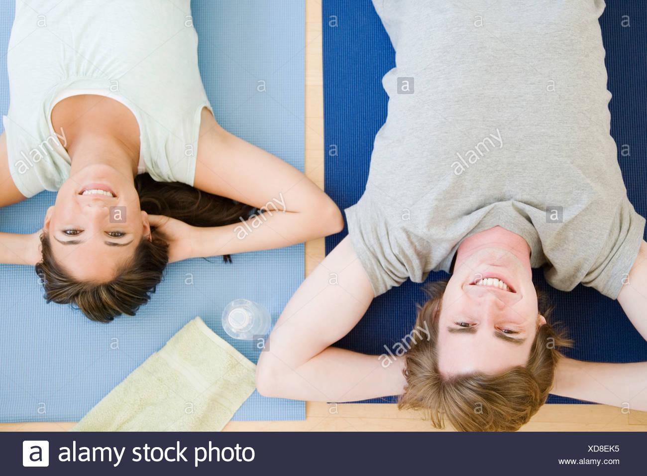 Couple laying on yoga mats - Stock Image