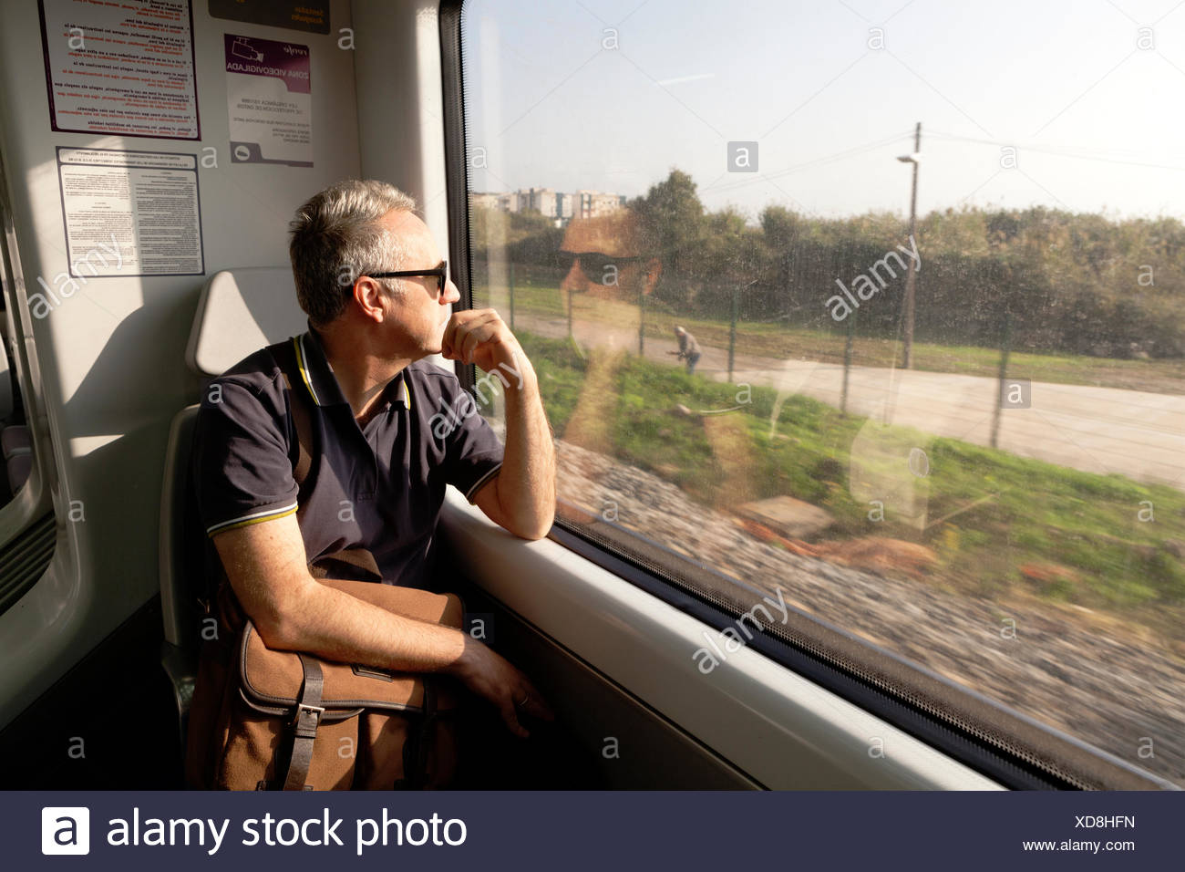 A man travelling on a train looking out the window Stock Photo - Alamy
