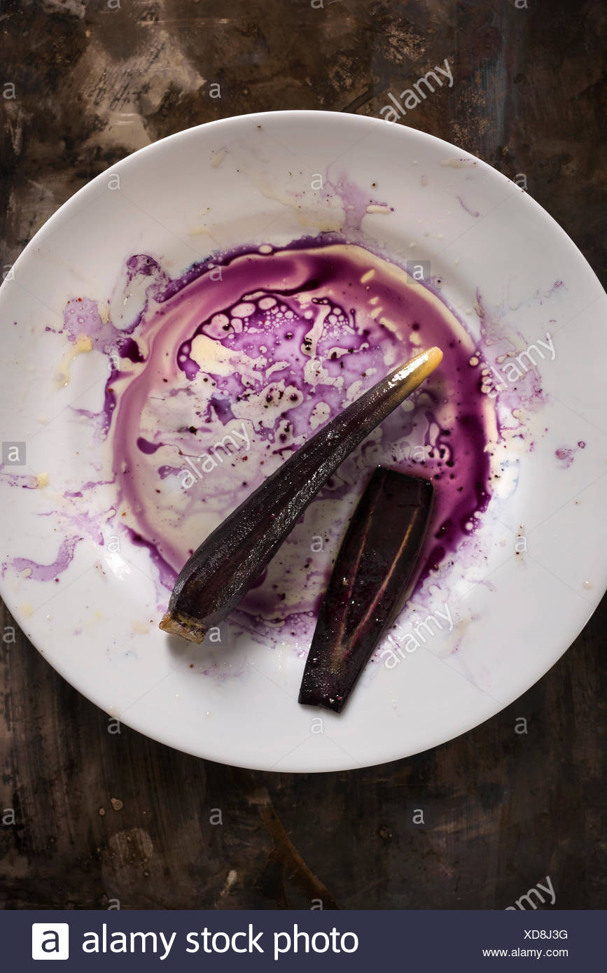 Purple carrot on a white plate with purple juices and oil creating a messy mixture all on a rustic metal surface. - Stock Image