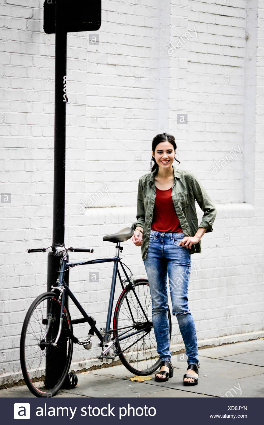 Woman standing beside bicycle Stock Photo