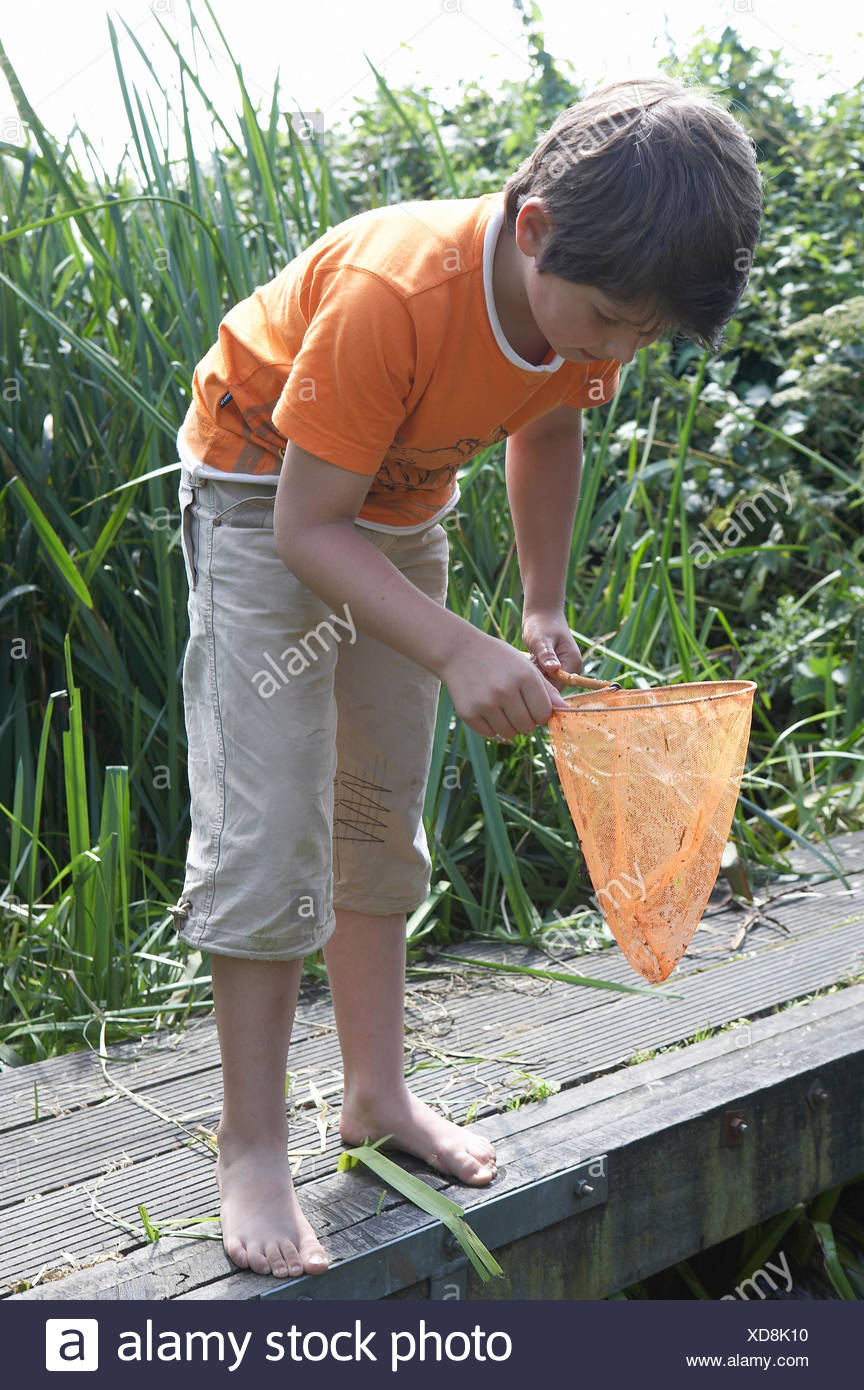 Barefooted young boy on wooden plank wearing orange t-shirt looking into his fishing net - Stock Image
