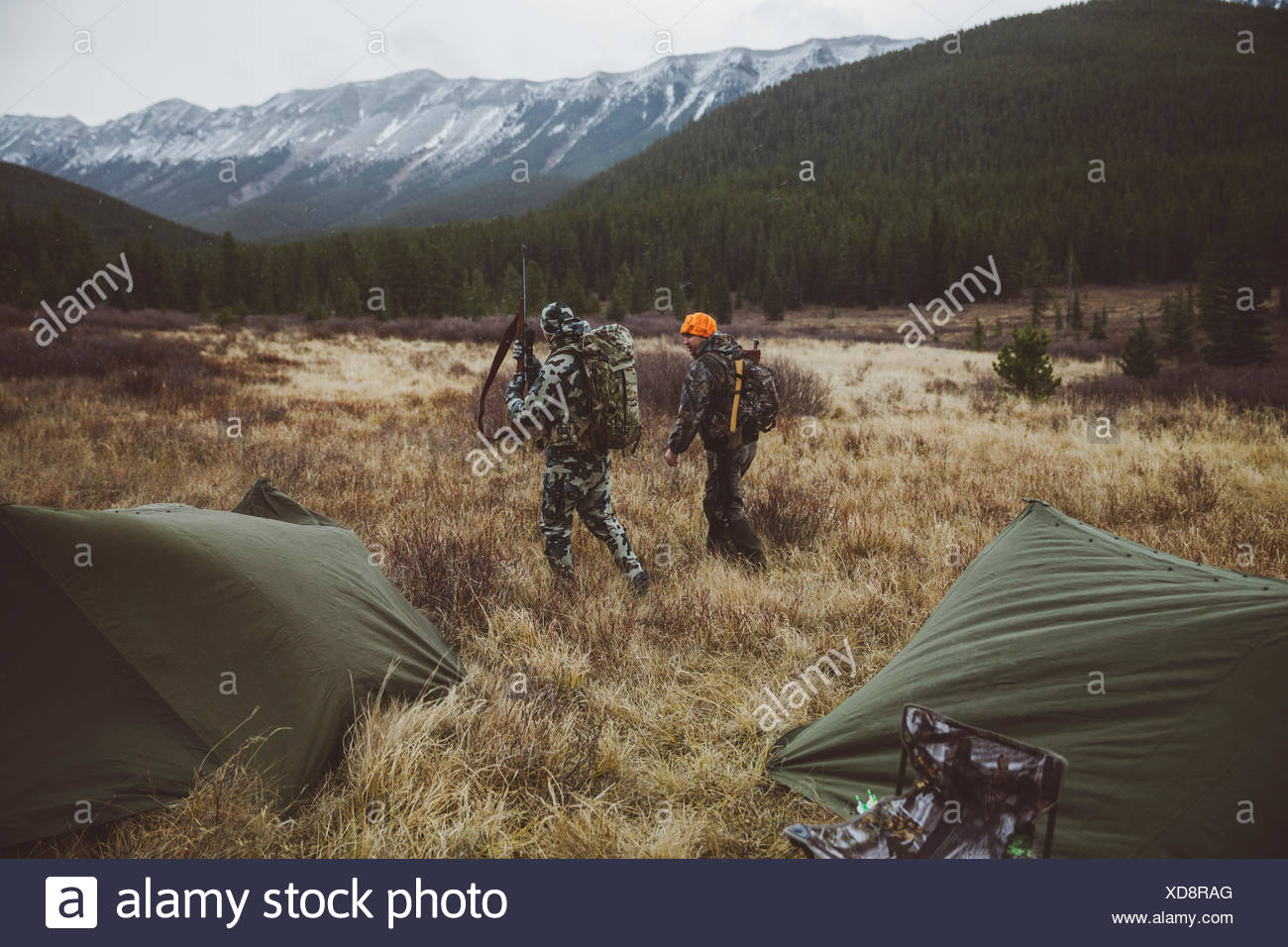 Male hunter friends walking outside tents at campsite in remote field below mountains - Stock Image
