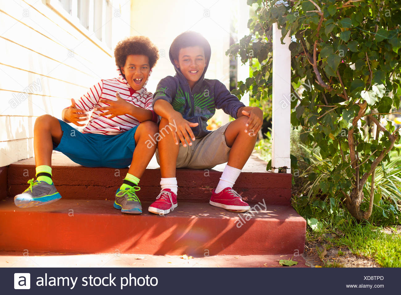 Portrait of two brothers sitting on porch steps - Stock Image
