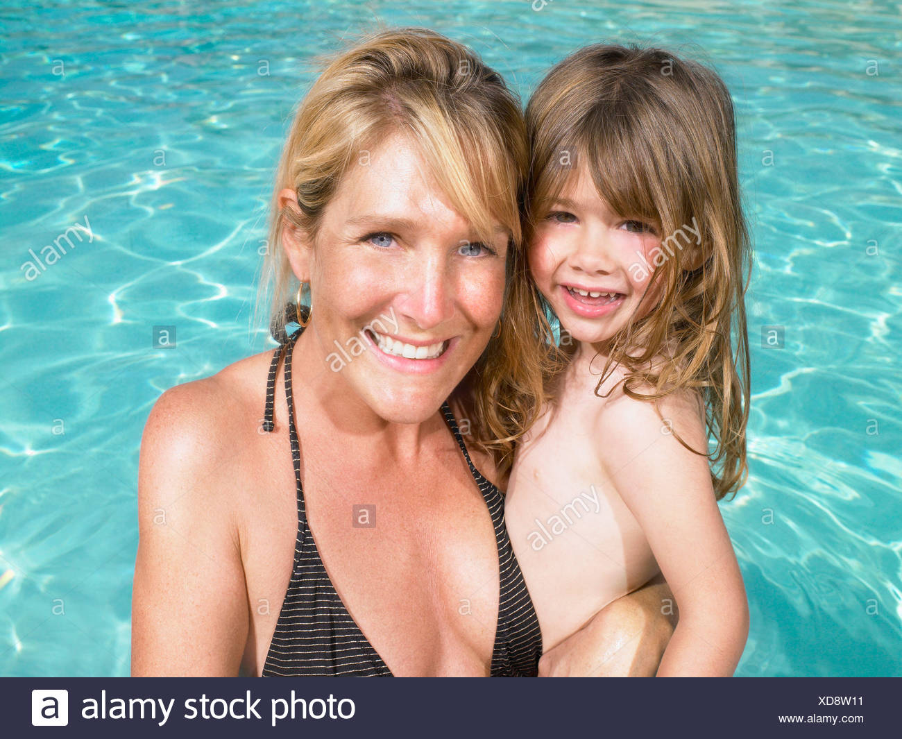 Mother and daughter in pool. - Stock Image