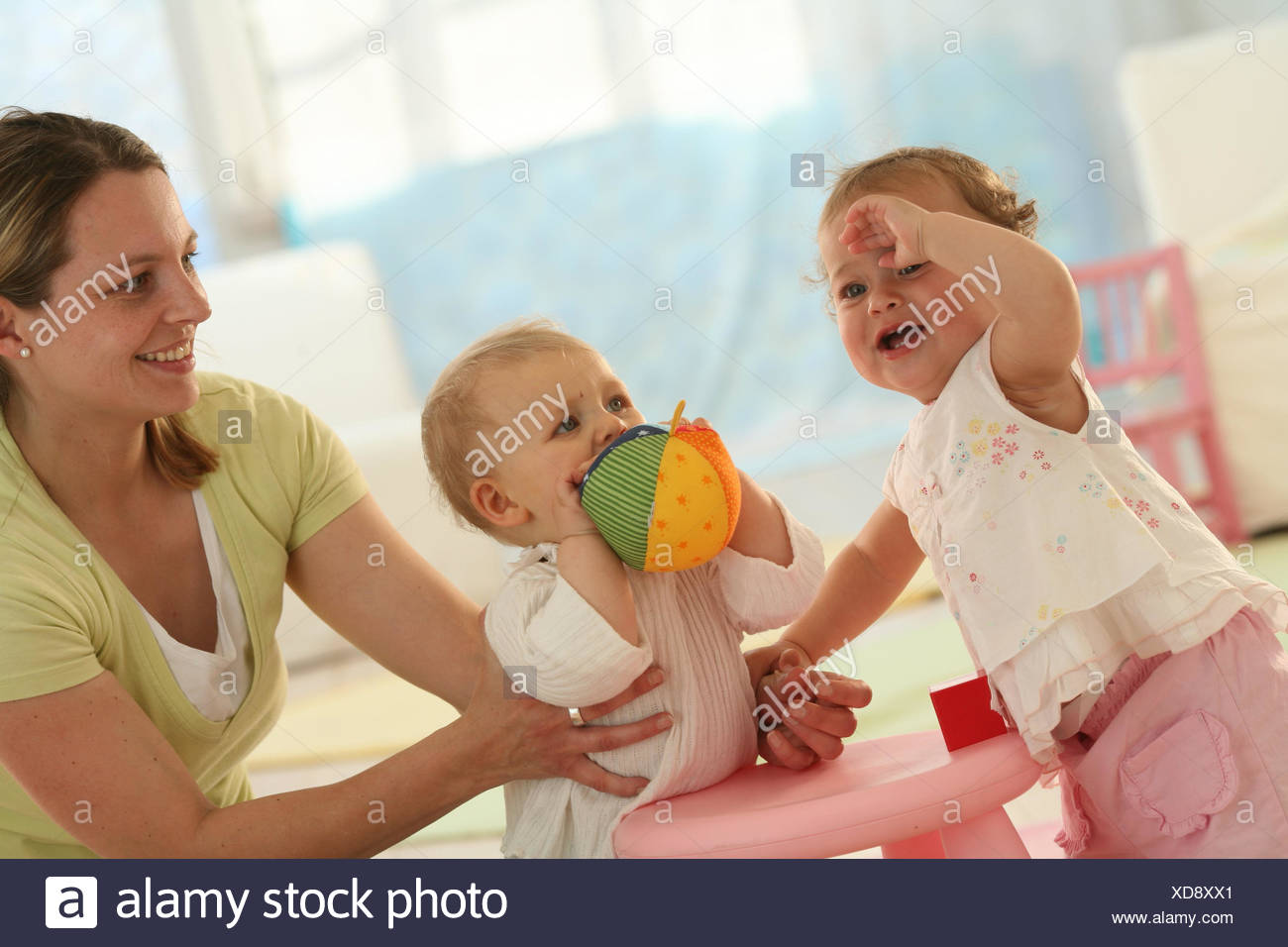 Babies, 9 months, mother, ball, play, get up, ball, dressed, blond, jealousy, discoveries, friends, reach, group, Indoor, boy, facial play, girl, play, toys, stand, fight, weep, baby, person, woman, - Stock Image