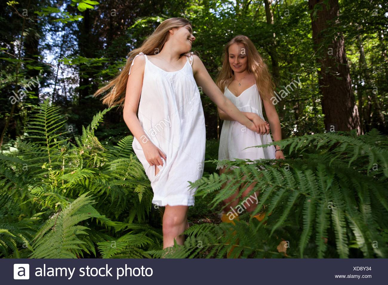 Two teenage girls wandering through forest - Stock Image